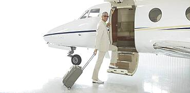 Middle-aged man boarding airplane in hanger