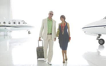 Couple walking in airplane hanger