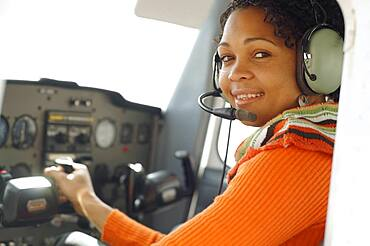 African woman in cockpit of airplane