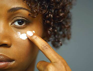 Close up of African woman applying cream under eye