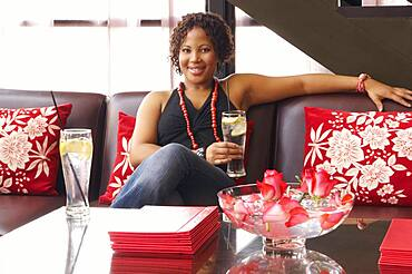 African American woman sitting on sofa with drink