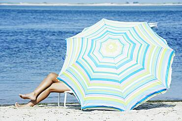 Woman sitting under beach umbrella