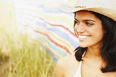 Woman wearing straw hat in field