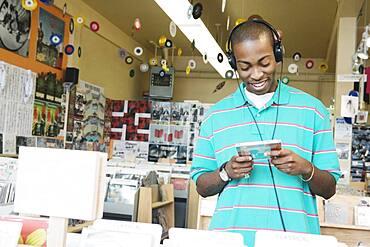 Teenage boy listening to headphones in a music store