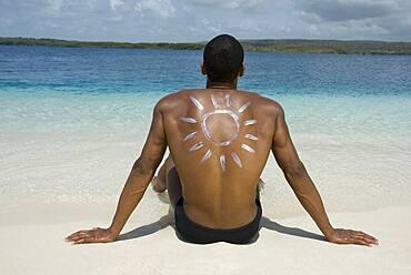 Hispanic man sitting on beach