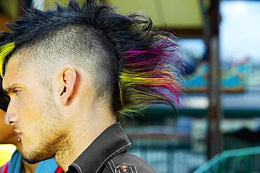 Profile of Hispanic male punk with mohawk hairstyle outdoors
