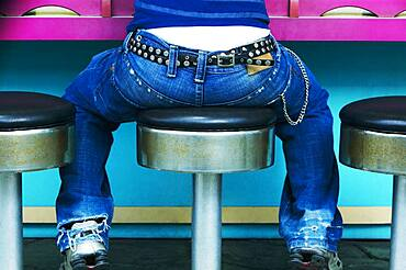 Rear view of young person with studded belt sitting on stool at counter