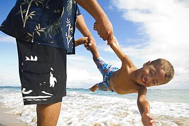 Pacific Islander father and son playing at beach