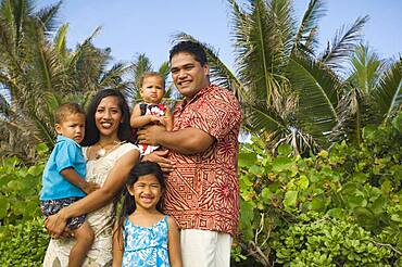 Pacific Islander family in front of palm trees