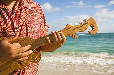 Pacific Islander man playing instrument at beach