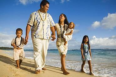 Pacific Islander family walking on beach