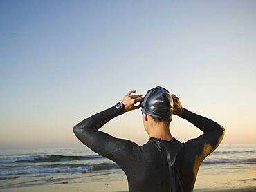 Rear view of Hispanic woman wearing wetsuit
