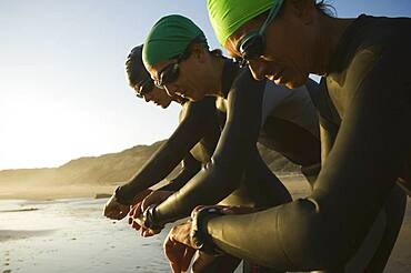 Multi-ethnic swimmers checking watches