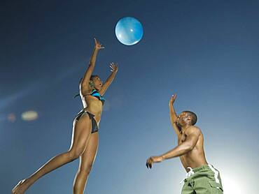 African American couple playing with beach ball