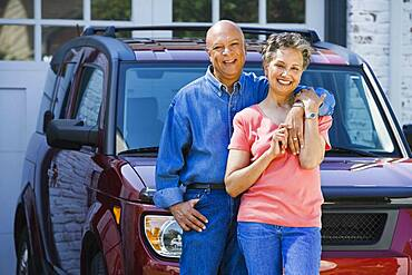 Senior African American couple leaning on car