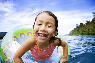 Asian girl swimming with inner tube