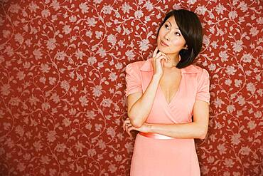 Asian woman thinking in front of floral wallpaper