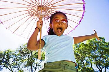 African American girl laughing with parasol outdoors
