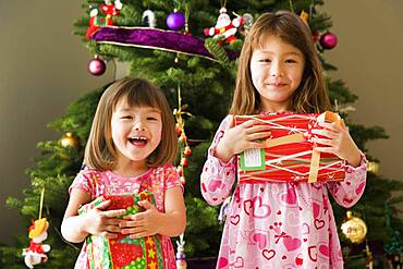 Two young sisters with Christmas presents