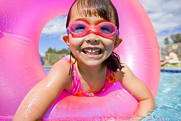 Portrait of girl in swimming pool wearing goggles