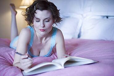 Woman laying on bed with pen and book