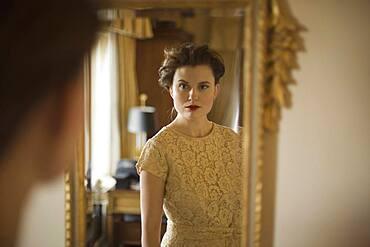 Woman wearing fancy dress looking in mirror