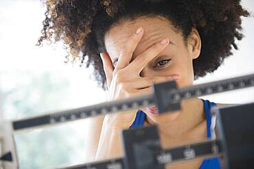 Mixed race woman hiding from weight on scale