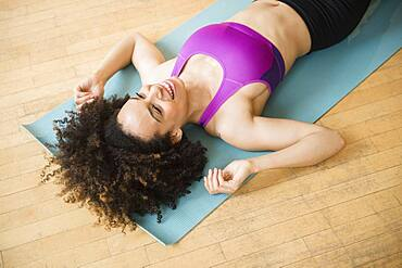Mixed race woman laying on exercise mat on floor