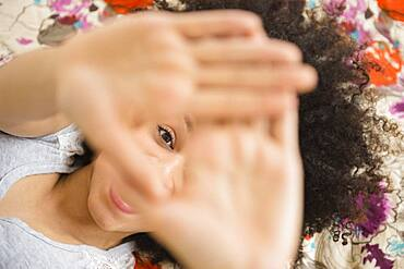 Mixed race woman peering through fingers on bed