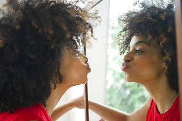 Mixed race woman puckering in mirror