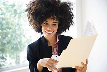 Mixed race businesswoman using cell phone near window