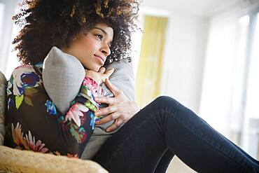 Mixed race woman hugging pillow in armchair