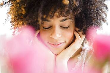 Mixed race woman resting chin in hands