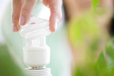 Mixed race woman holding fluorescent light bulb