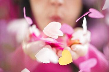 Mixed race woman blowing confetti hearts