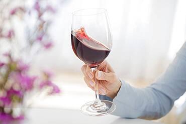 Mixed race woman swirling glass of wine