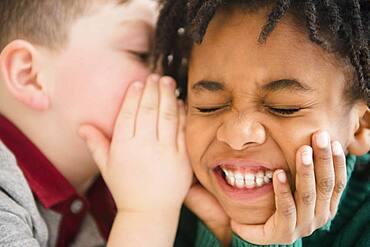 Close up of boys whispering secrets