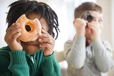 Boys peering through donut holes