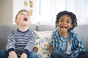 Boys laughing on living room sofa