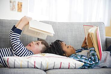 Boys reading on living room sofa