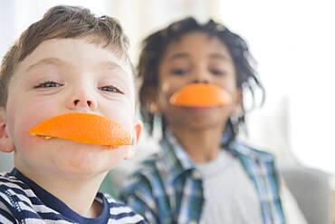 Boys biting orange slices