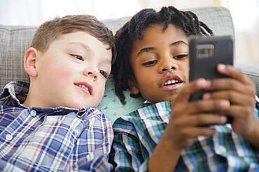 Boys using cell phone on sofa