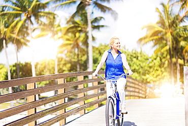 Caucasian woman riding bicycle on bridge