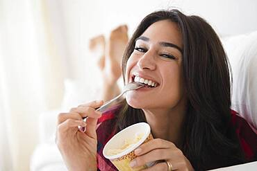 Close up of woman eating ice cream on sofa