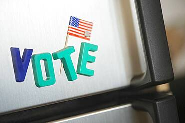 Close up of vote magnets and American flag on refrigerator
