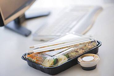 Close up of take-out lunch near computer