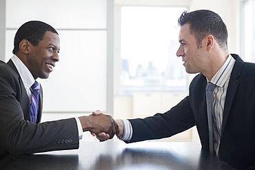 Businessmen shaking hands in office meeting