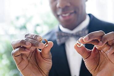 Close up of groom holding wedding rings