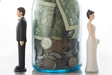 Close up of bride and groom dolls near savings jar