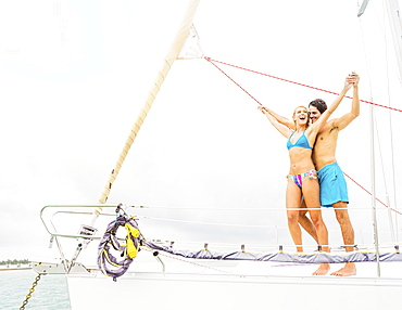 Couple standing on deck of sailboat